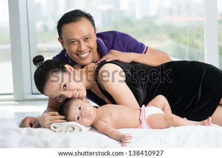 Portrait of a young family with a male newborn inside - stock photo