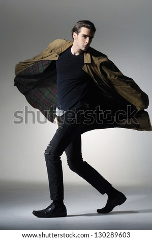 portrait of a young fashion male walking on light background - stock photo