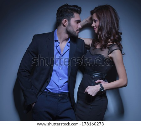 portrait of a young fashion woman being held by a handsome man while they are looking into each other's eyes. on a dark blue background - stock photo