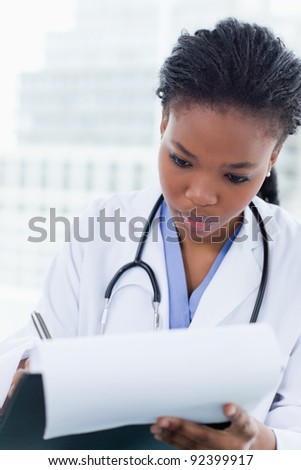 Portrait of a young female doctor signing a document in her office - stock photo