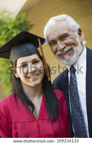 Portrait of a young female graduate with grandfather smiling - stock photo