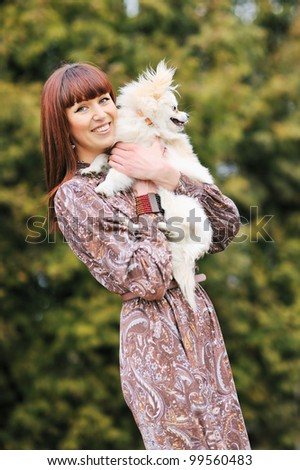 Portrait of a young female hugging a cute puppy - stock photo