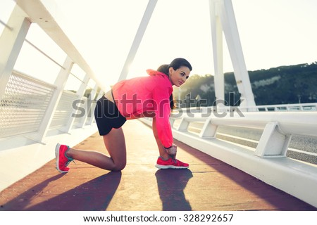 Portrait of a young female jogger dressed in sportswear tie shoelaces while taking break between evening run outside, athletic woman resting after fitness training outdoors during recreation time  - stock photo