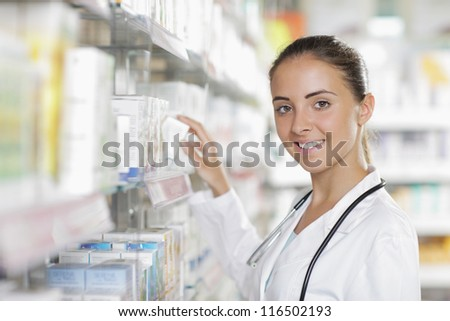 Portrait of a young female pharmacist selecting a medication - stock photo
