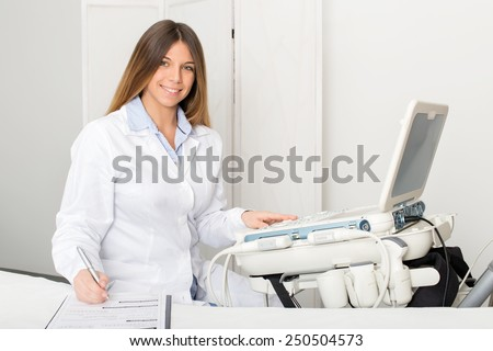 Portrait of a young female radiologist sitting by ultrasound machine while smiles and writes on a medical information form - stock photo