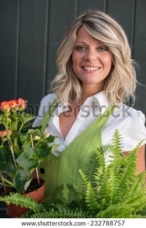 Portrait of a young florist arranging flowers - stock photo