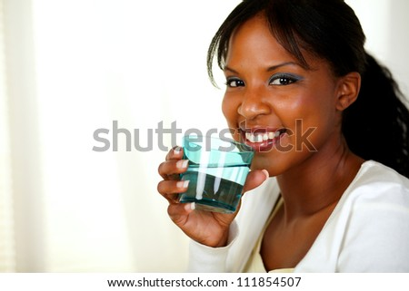 Portrait of a young friendly healthy lady smiling and drinking fresh water while looking at you. With copyspace. - stock photo