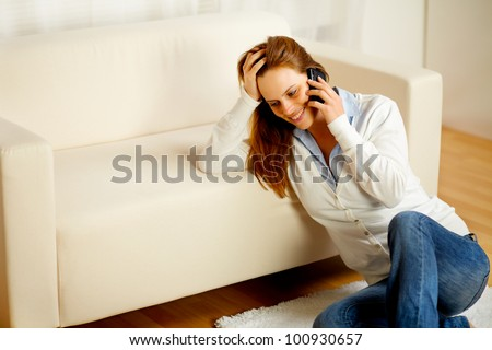 Portrait of a young friendly woman having fun on mobile phone at home - stock photo