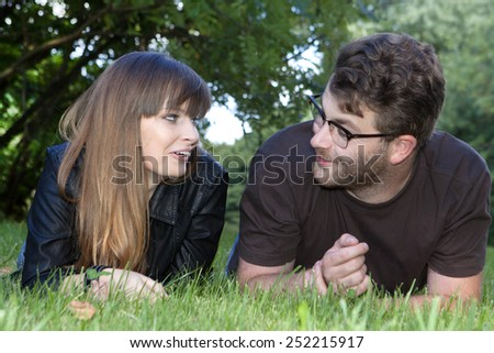 portrait of a young friends laying down on green grass in a sunny park  - stock photo