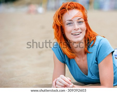 Portrait of a young funny happy redhead woman on the beach lying on a sand, - stock photo