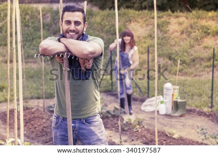 portrait of a young gardener relaxes in her greenhouse - stock photo