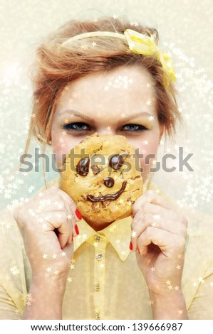 Portrait of a young girl and a smiling chocolate chip cookie surrounded by little golden stars - stock photo