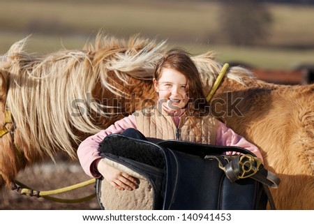 Portrait of a young girl carrying saddle with her palomino horse in the background - stock photo