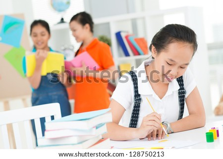 Portrait of a young girl drawing in the foreground - stock photo
