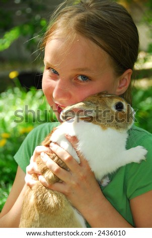 Portrait of a young girl holding a bunny outside - stock photo
