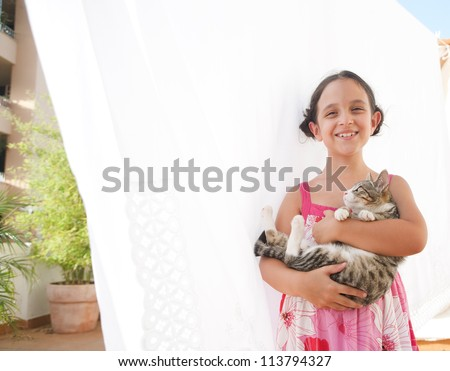 Portrait of a young girl holding a cat in her arms and smiling at the camera, while standing next to white linen hanging to dry on a terrace. - stock photo