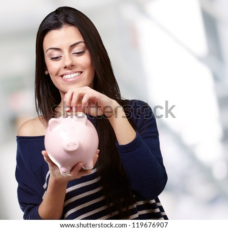 Portrait Of A Young Girl Holding A Piggy Bank, Background - stock photo