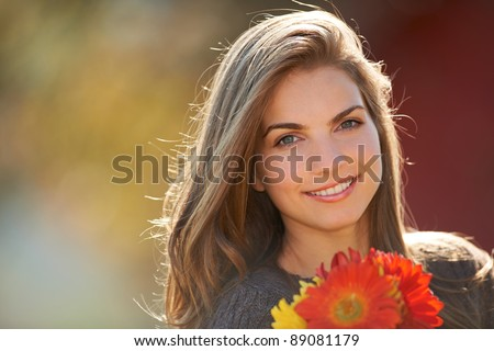 Portrait of a young girl holding red flowers outdoors. - stock photo