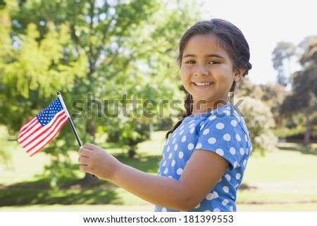 Portrait of a young girl holding the American flag at the park - stock photo