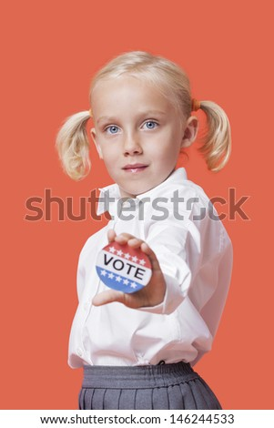 """Portrait of a young girl holding """"Vote"""" sign over orange background - stock photo"""