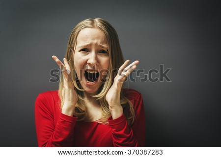 Portrait of a young girl in a red dress on a gray background. Frightened shocked scared woman - stock photo