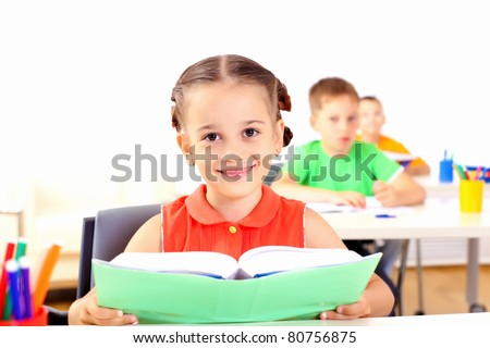 Portrait of a young girl in school at the desk. - stock photo