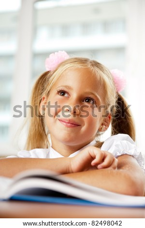 Portrait of a young girl in school at the desk. Vertical Shot. She is looking and listening at her teacher attentively. - stock photo