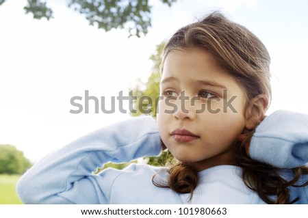Portrait of a young girl in the park with an unhappy expression. - stock photo