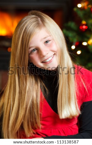 portrait of a young girl on christmas eve christmas tree in background - stock photo