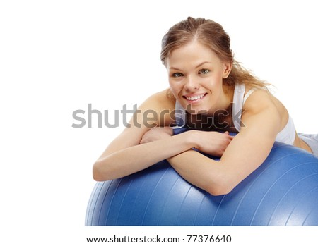 Portrait of a young girl on gymnastic ball looking at camera and smiling - stock photo
