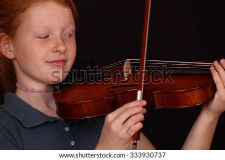 Portrait of a young girl playing violin on black background - stock photo