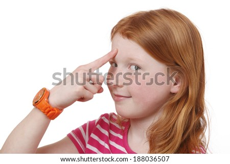 Portrait of a young girl pointing with finger at forehead on white background - stock photo