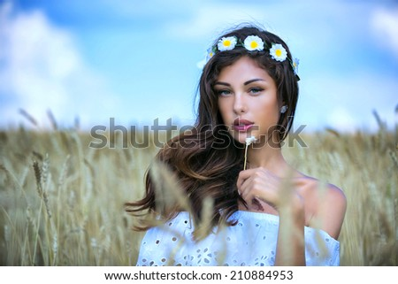 Portrait of a young girl sitting in a wheat field - stock photo