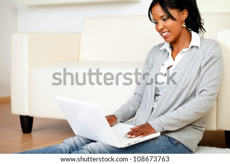 Portrait of a young girl smiling and browsing the Internet at home with her laptop while is sitting on the floor - stock photo