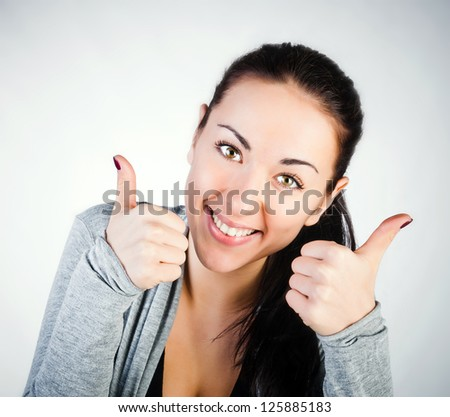 portrait of a young girl smiling brunette with a thumbs up - stock photo