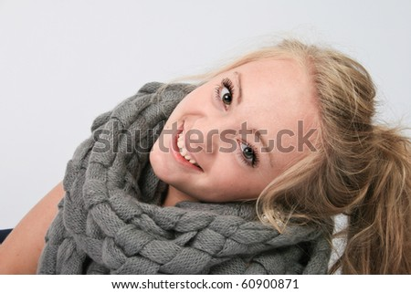 portrait of a young girl with a gray knitted scarf - stock photo