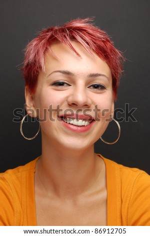 portrait of a young girl with red hair in front of a chalkboard - stock photo