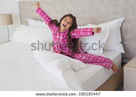 Portrait of a young girl yawning while stretching her arms in bed at home - stock photo