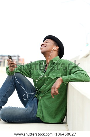 Portrait of a young guy sitting outdoors listening to music on mobile phone with earphones - stock photo