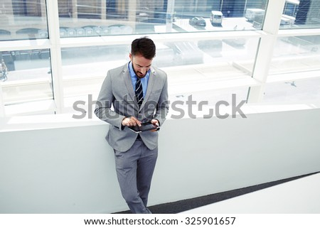 Portrait of a young handsome businessman in formal wear working on touch pad while standing in modern office space, confident man boss dressed in luxury clothes using digital tablet during work break  - stock photo