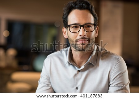 Portrait of a young handsome businessman wearing glasses. Close up of smiling business man wearing eyeglasses. Thinking business man wearing glasses sitting in office.  - stock photo