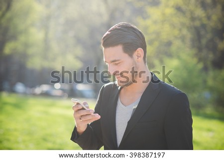 Portrait of a young handsome caucasian man using a smart phone connected online, looking down and tapping the screen- technology, social network concept - stock photo