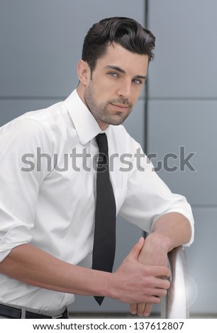 Portrait of a young handsome confident businessman - stock photo