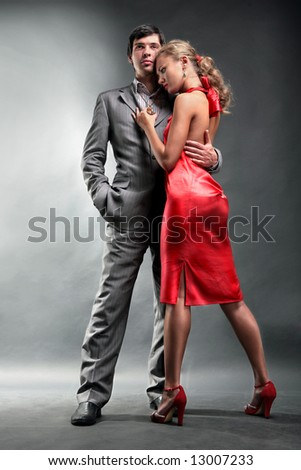Portrait of a young handsome couple. Young woman embraces man. Woman in a red dress - stock photo