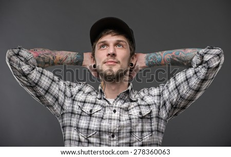 portrait of a young handsome guy, holding his hands behind his head and looks up. youth style , isolated on black background - stock photo