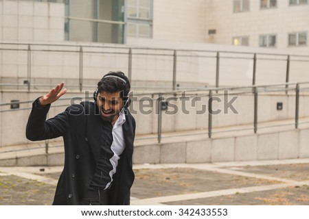 Portrait of a young handsome Indian man with headphones listening to music in an urban context - stock photo
