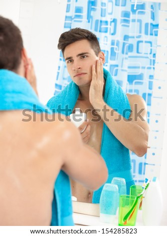 Portrait of a young handsome man applying after shave - stock photo