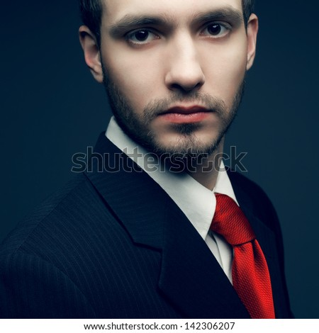 Portrait of a young handsome man (businessman) in black classic suit with trendy red tie. Close up. Studio shot - stock photo