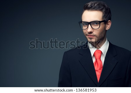 Portrait of a young handsome man (businessman) in black suit with trendy pink tie, stylish glasses smiling and looking at camera. Copy-space. Studio shot - stock photo