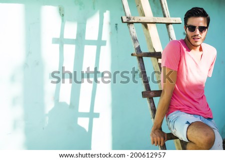 Portrait of a young handsome man, fashion model,  in urban background - stock photo